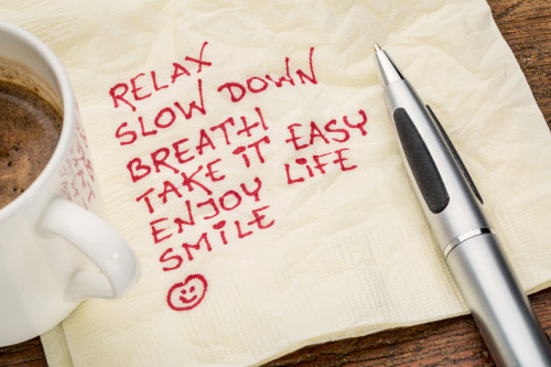 Picture of a cup of coffee with a pen and napkin with handwritten note: Relax, slow down, breath, take it easy, enjoy life, smile.