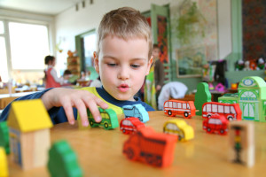 Kindergarten child plays with toy trucks on a table